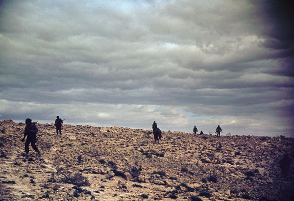 US infantry soldiers trudge across a hill in the desert in the El Guettar Valley, Tunisia, early 1943
