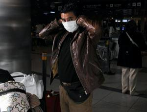 A passenger takes precautions at Ezeiza International Airport, Argentina, as the swine flu pandemic intensifies