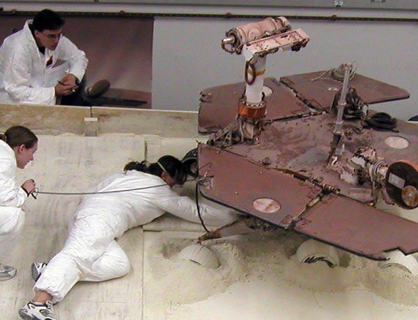Researchers at JPL simulated the conditions faced by the rover Spirit on Mars, where it is stuck in loose soil, to find the best way to help free it