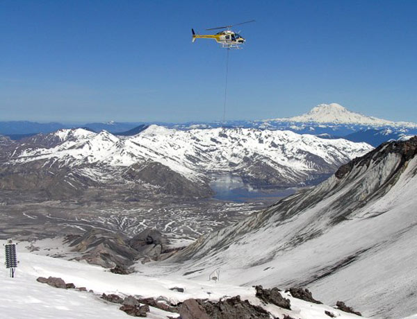 A helicopter drops off an earlier version of a spiderbot in the crater of Mount St Helens in 2006