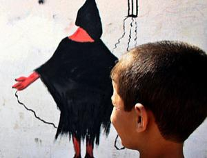 In Baghdad, a boy stares at a wall painting of the well-known photograph of an abused Iraqi prisoner at Abu Ghraib prison