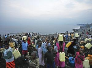 Congolese people carry buckets of water on the bank of Lake Kivu in Goma. The lake contains a vast reservoir of dissolved methane