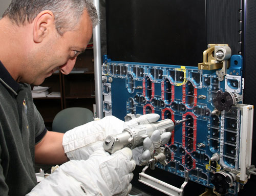 Astronaut Mike Massimino wears space gloves while practising a tricky repair of Hubble's STIS instrument before the final mission to service the telescope last May