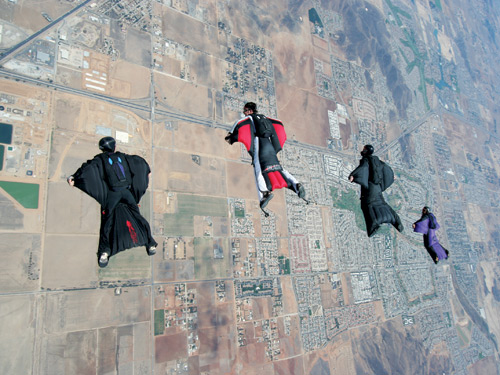 Jeb Corliss (Black suit, right of centre) makes another jump