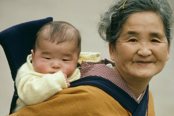 An older Japanese woman carrying a baby on her back