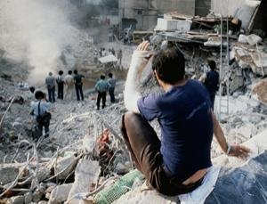Person with arm in cast looking down on an expanse of rubble, smoke and twisted wires