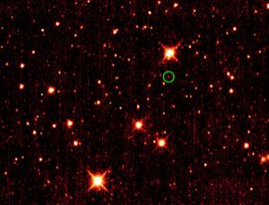 Earth's first Trojan asteroid (circled) appears against a backdrop of distant stars and galaxies in this WISE image taken in October 2010