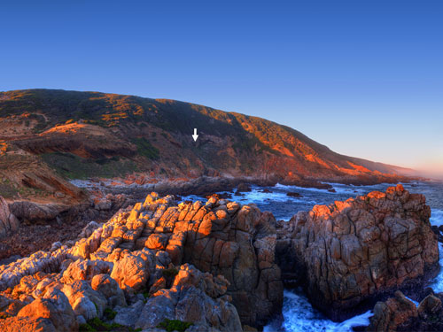 The entrance of Blombos cave on the coast of the Indian Ocean