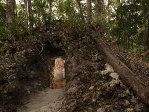 The painted figure of a man is illuminated through this doorway in northeastern Guatemala, the first ancient Mayan house found to contain artwork on its walls.