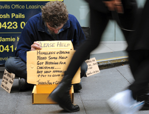 Man sitting on pavement holding a cardboard sign with downcast head