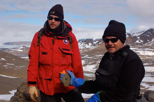 Joe Kirschvink (right) holds a gastropod fossil, Tom Tobin