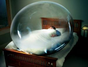 A person asleep in bed and enclosed in a big bubble