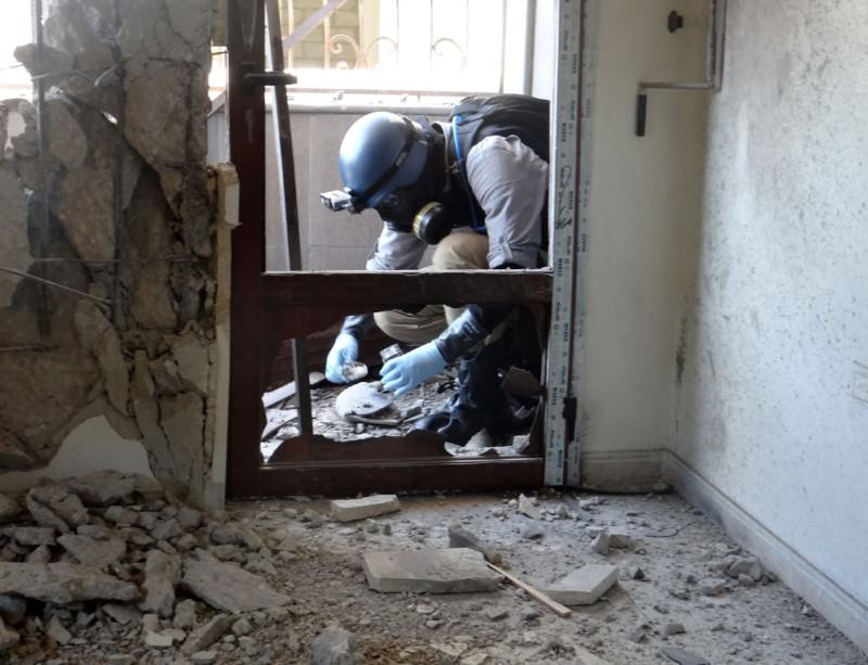 A UN investigator collecting samples last week at the site where rockets fell in Damascus's eastern Ghouta suburb