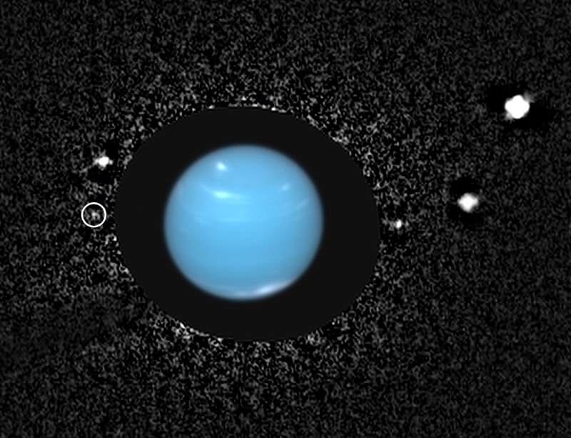 Naiad, circled at left, sits close to Neptune in this Hubble image