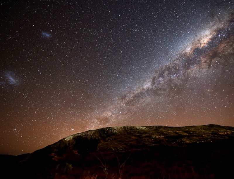 The Milky Way and its satellite galaxies, the Magellanic Clouds, rising above the hills of Azul in Argentina