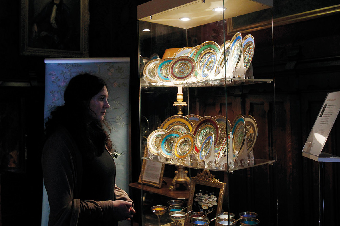 A women observes some China plates in a museum