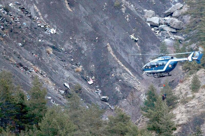 A helicopter circles the wreckage in the foothills of the Hautes-Alpes