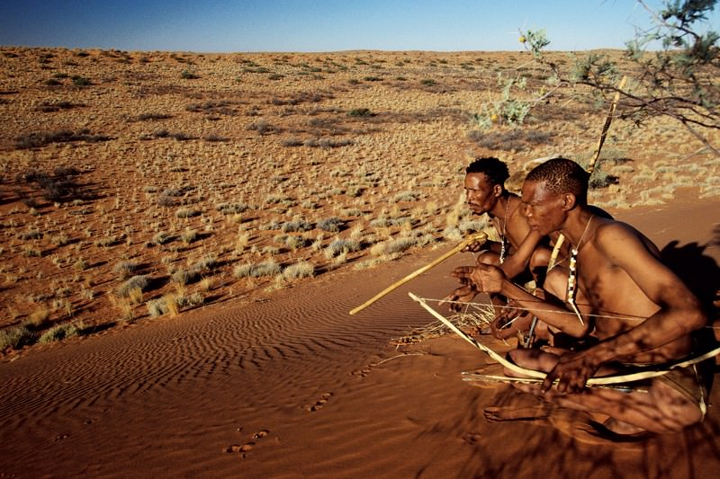 Two men in a desert with bows and arrows