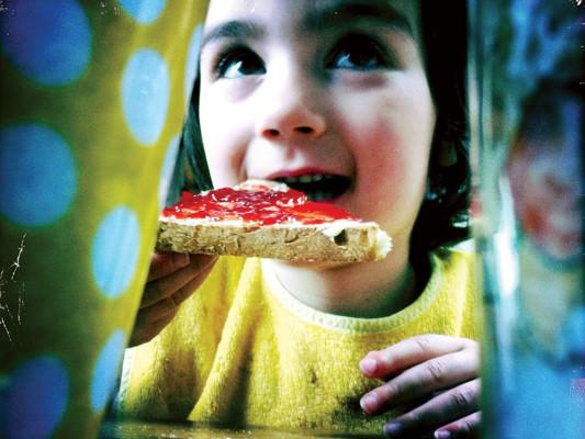 Girl eating jam sandwich
