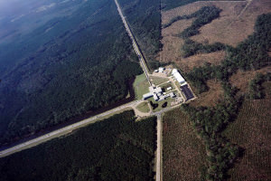 An aerial view of the LIGO Observatory. Medium size official looking building surrounded by woods