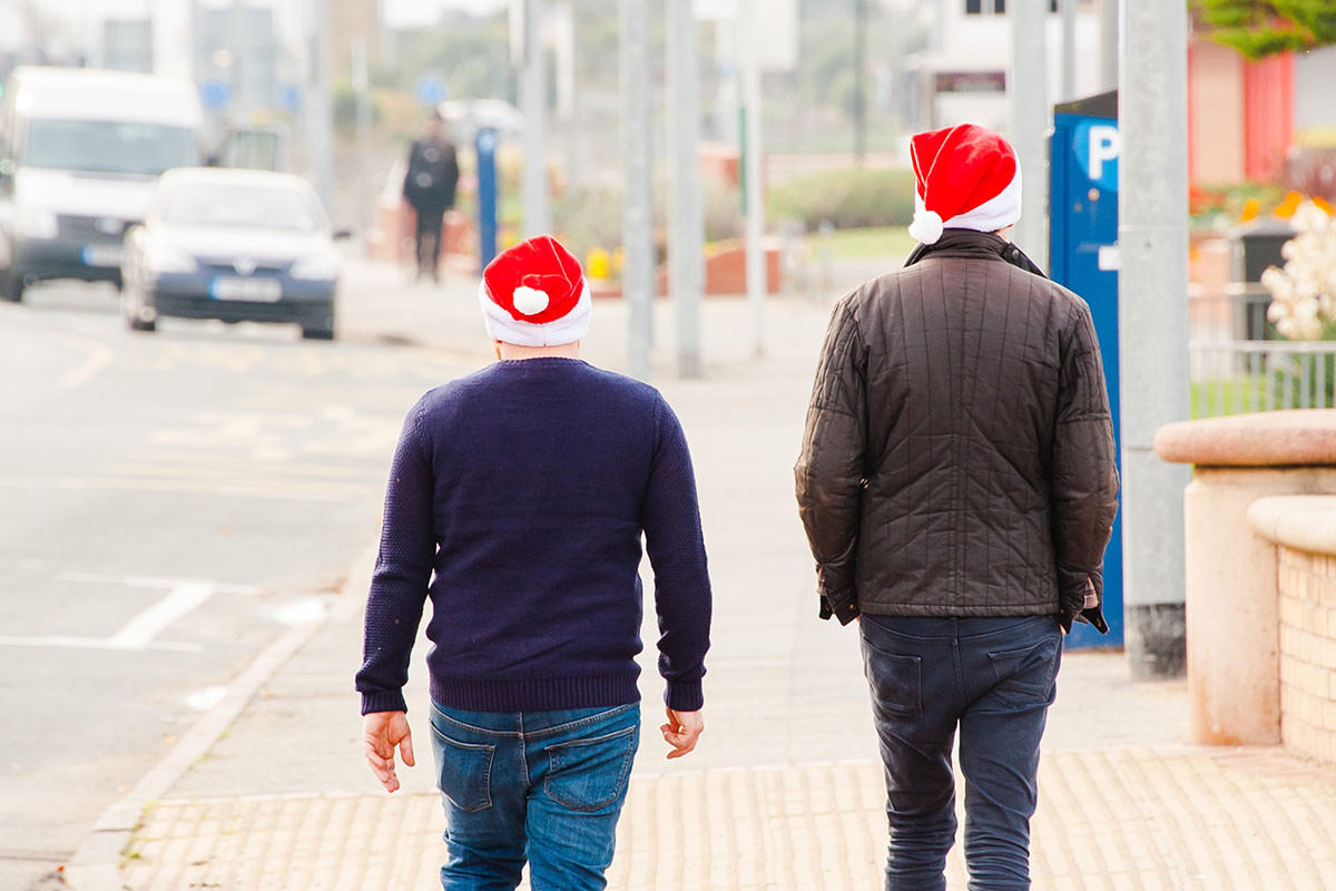 two men walking away down the street wearing santa hats. The connection to the story is marginal