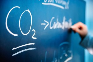 The formula for carbon dioxide drawn on a chalkboard