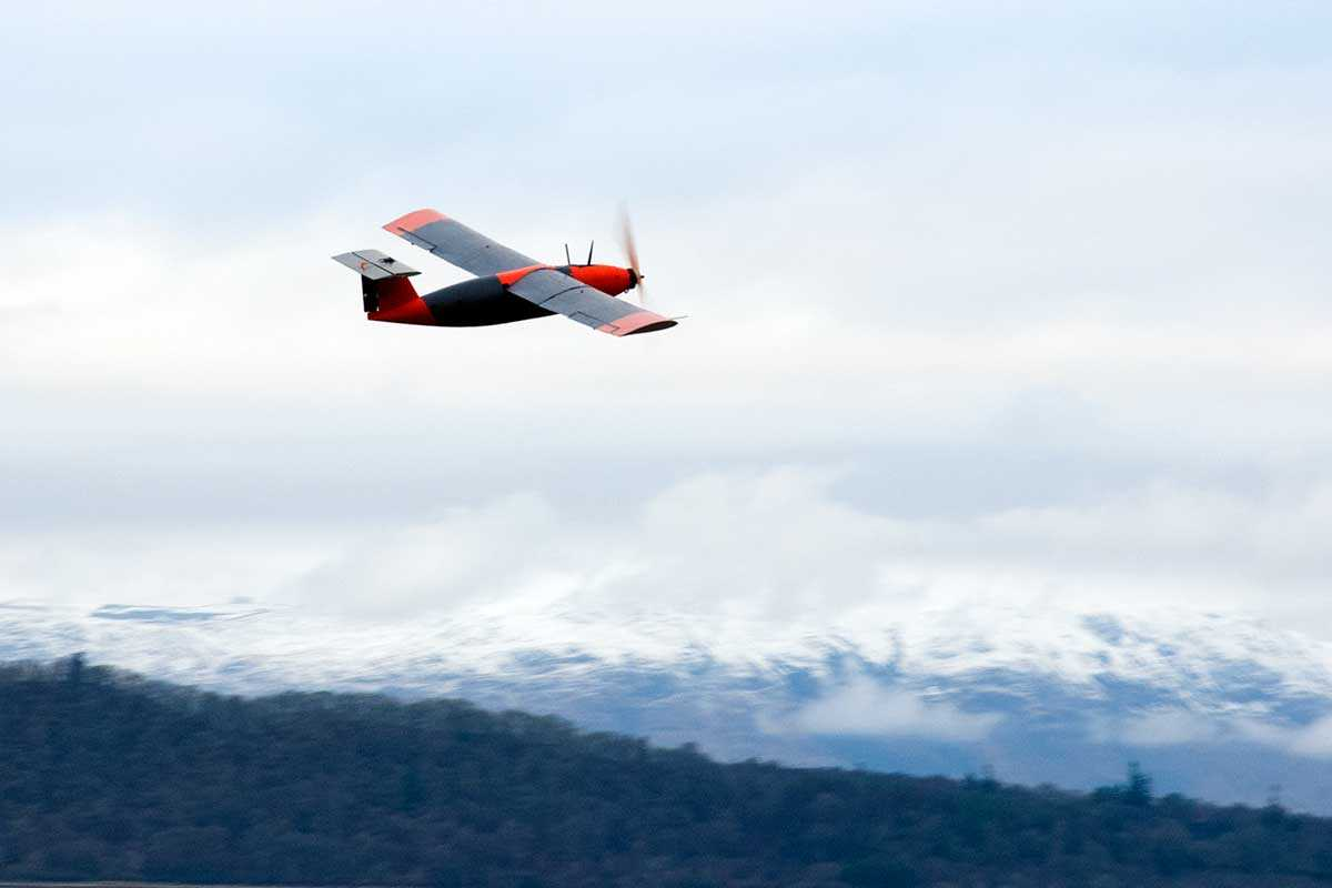 Fixed-wing drone flying against a snowy backdrop