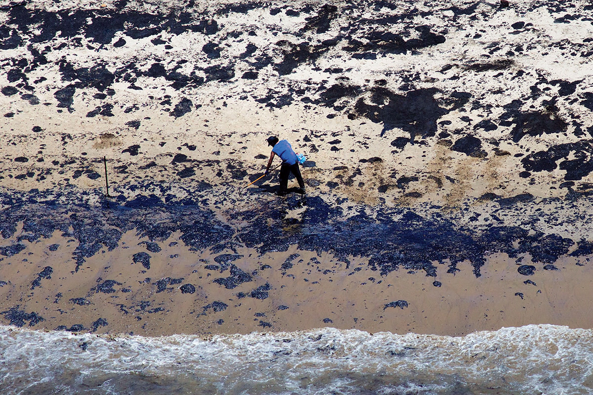 Overhead view of the oily surface of a beach, with a person clearing up