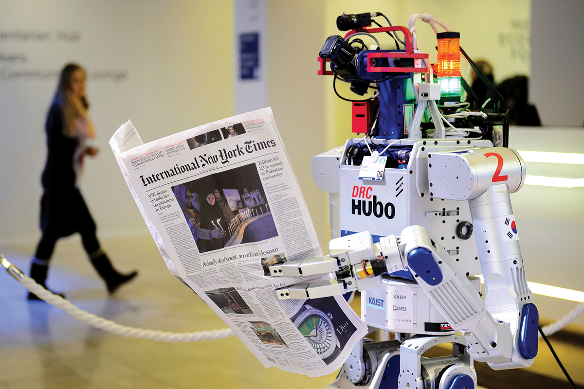 DRC Hubo robot holding a copy of the International New York Times newspaper