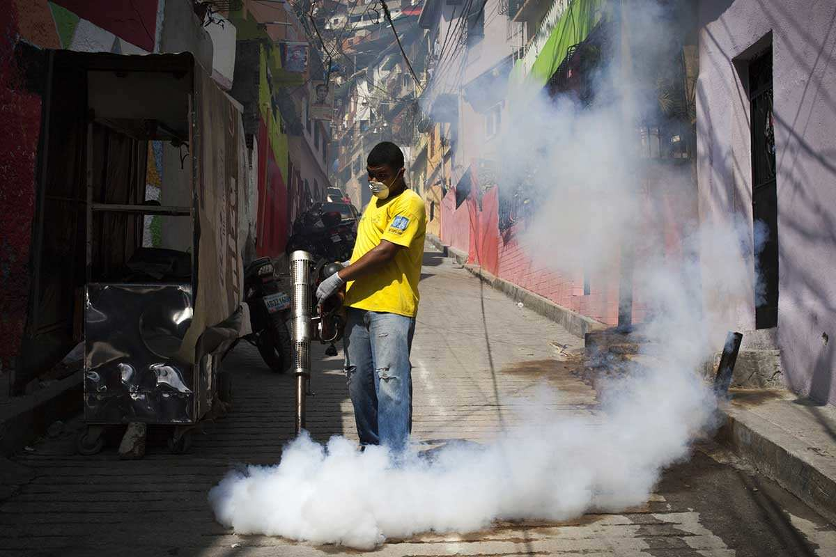 A man spraying mosquito-killing smoke