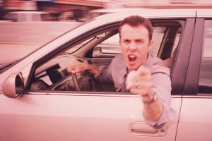 An angry man leaning out of a car and gesticulating at the camera