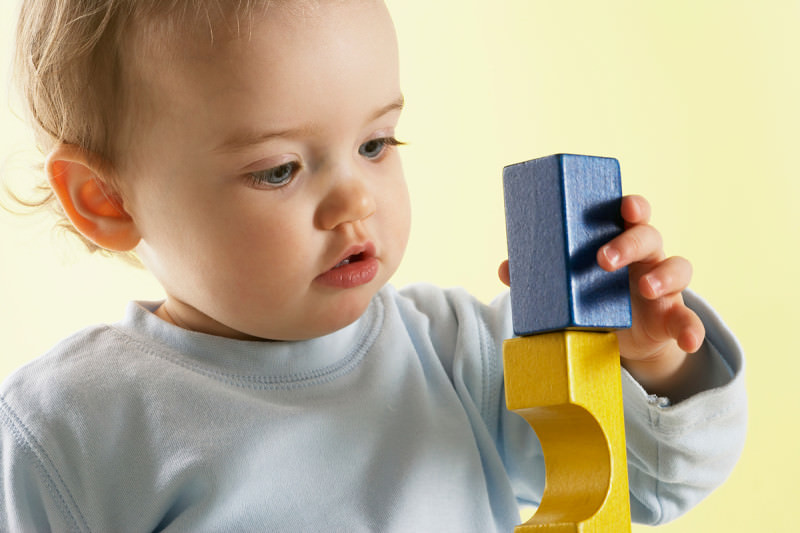 A toddler playing with wooden blocks