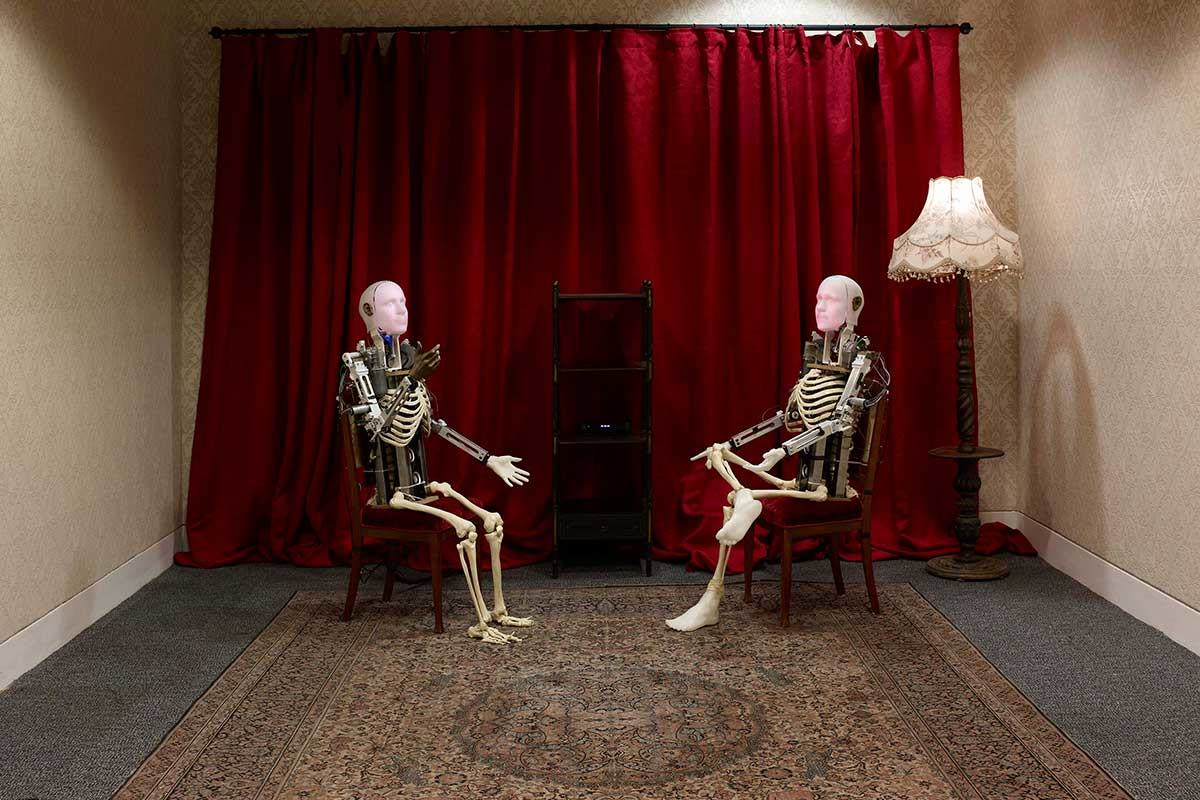Two skeletal androids talking to each other seated, in Talk by Tove Kjellmark, in The Imitation Game exhibition at Manchester Art Gallery