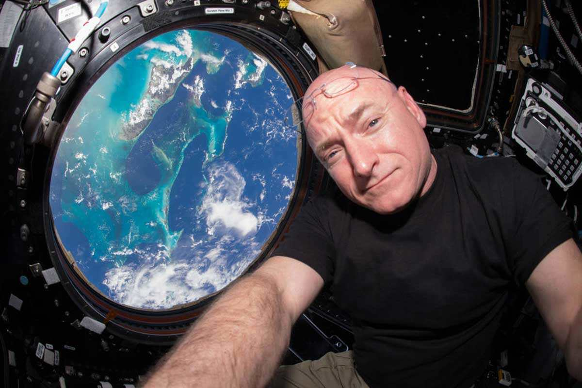 Scott Kelly selfie on the International Space Station, with a view of Earth out the window behind him
