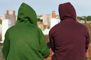 People wearing hoodies with their backs to the camera looking out over rooftops