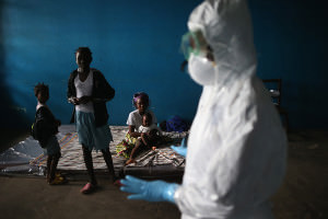 Masked health worker addresses people in makeshift isolation ward in Liberia