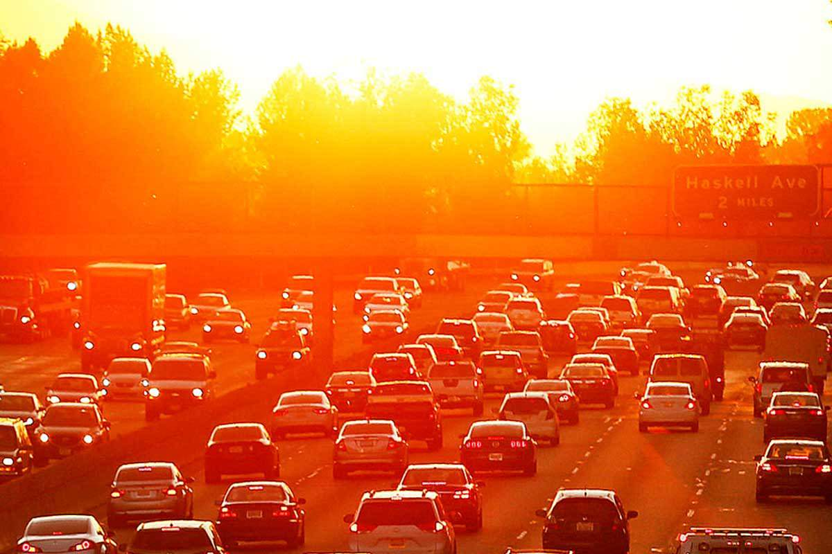 Jam of cars going both ways on a five-lane highway in LA, with the sun in the background making everything glow and giving an aura of hot, hot, hotness