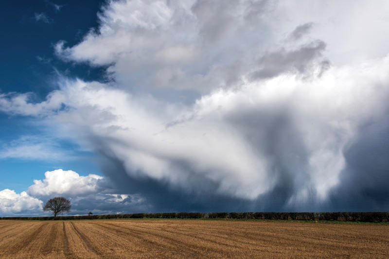 Rainclouds roll in over a field
