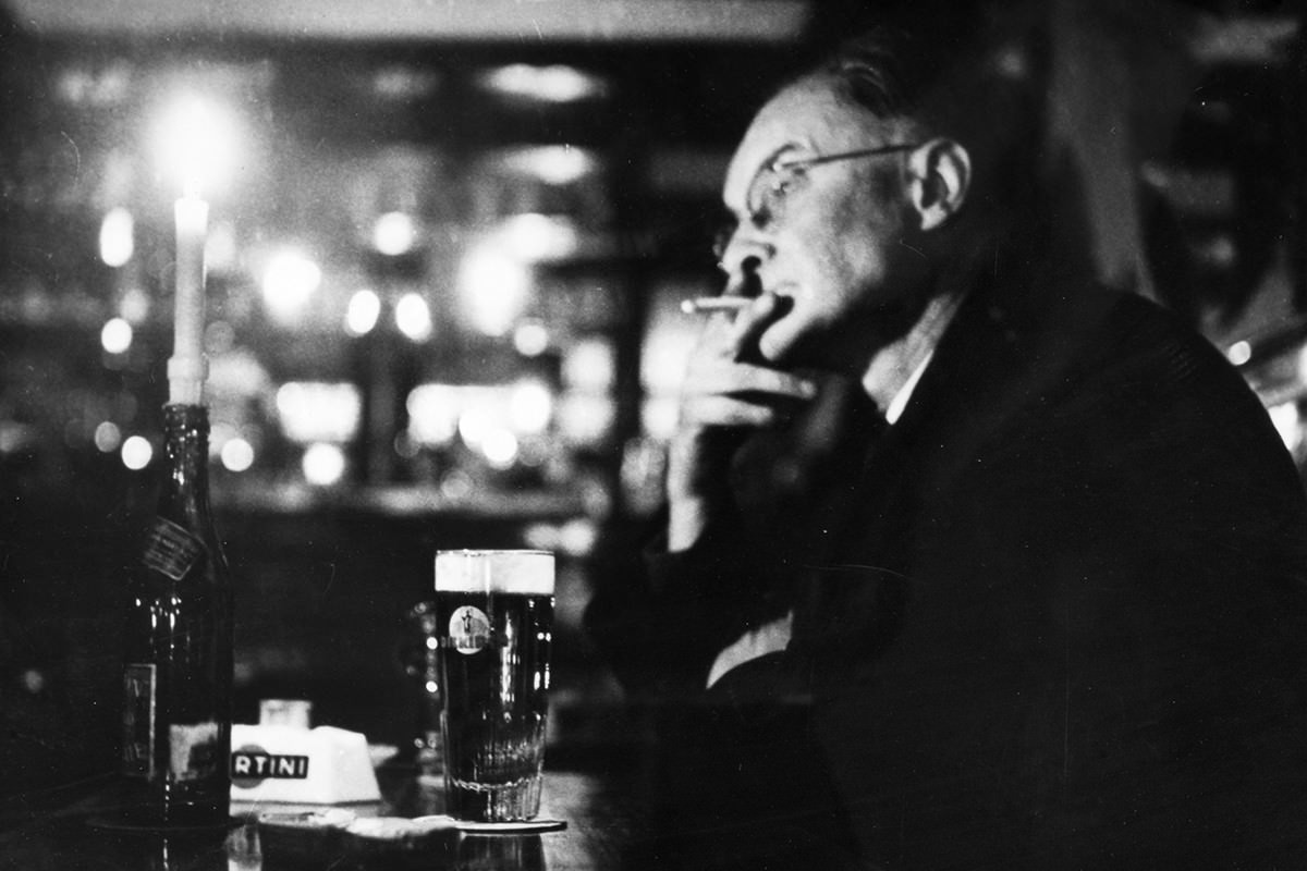 Older man smoking and drinking in a pub