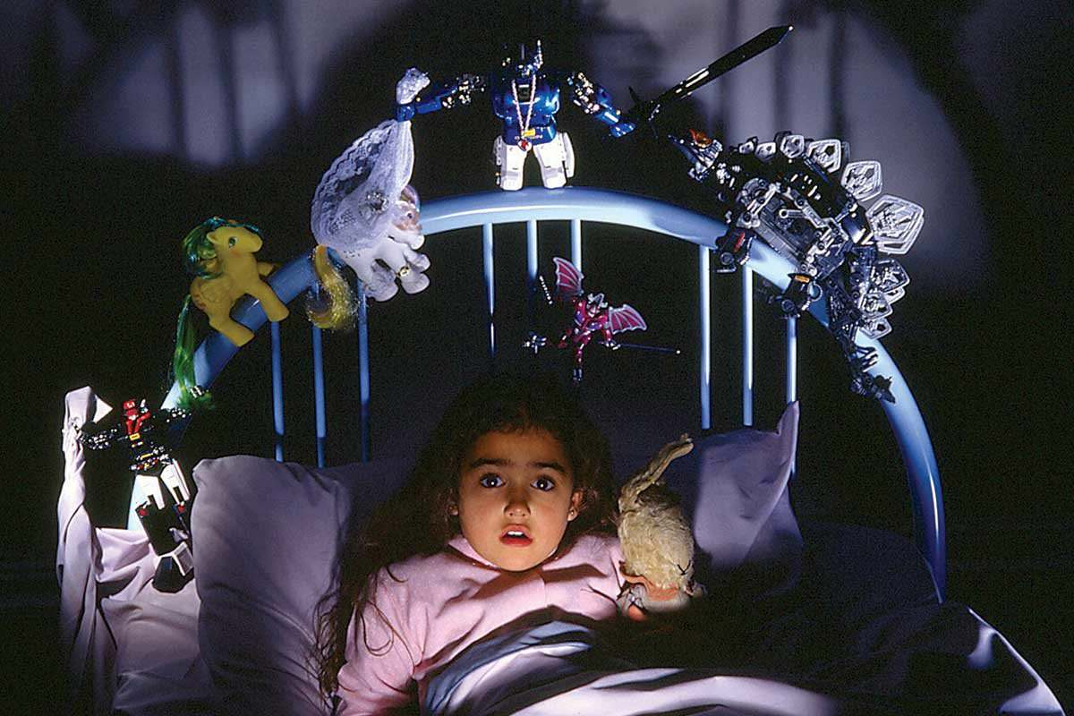 A girl in bed surrounded by scary toys