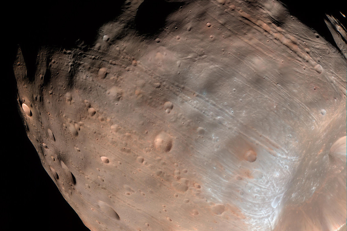 Brown pockmarked and streaked surface of Phobos