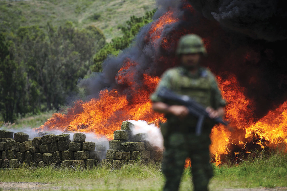 Armed soldier stands guard with rectangular packs ablaze in the background