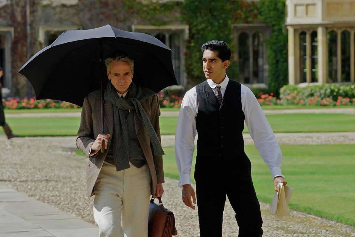 G. H. Hardy (Jeremy Irons) and Srinivasa Ramanujan (Dev Patel) walk together, deep in conversation