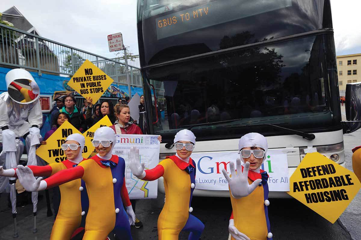 Protesters in colourful outfits stand in front of a bus that says Gbus to MTV on it