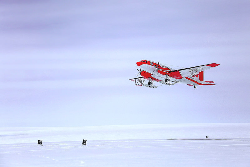 A plane flies over the icey Antarctic landscape