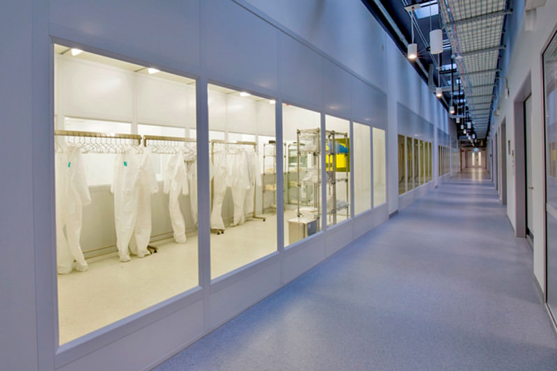 A view of a corridor inside, with sterile suits hanging up behind a window