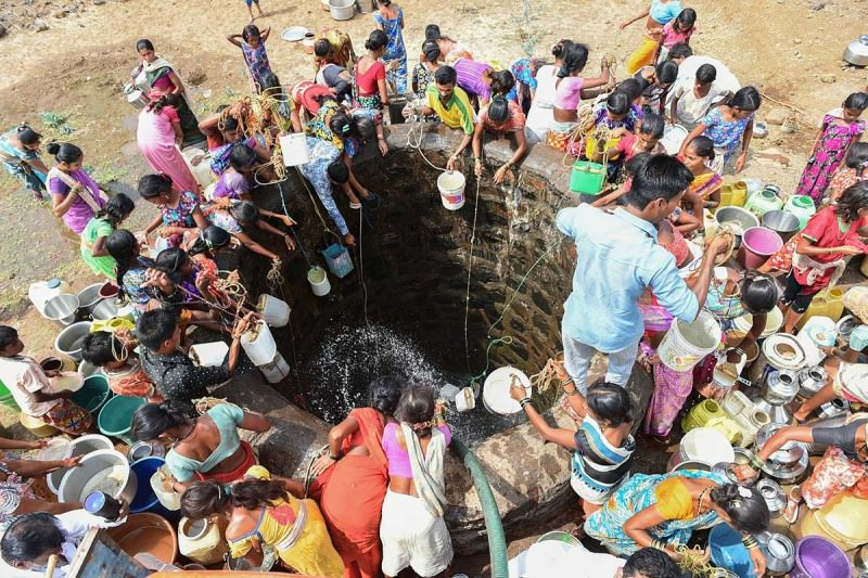 Indian villagers throw containers attached to ropes into a well to collect their daily supply of potable water after a tanker made its daily delivery at Shahapur, some 130 km southwest of Mumbai, on May 13, 2016
