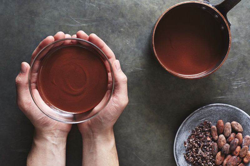 Someone holds a bowl of a cocoa drink