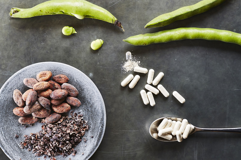 Some broad beans, nuts and seeds arranged on a table beside a handful of white capsules