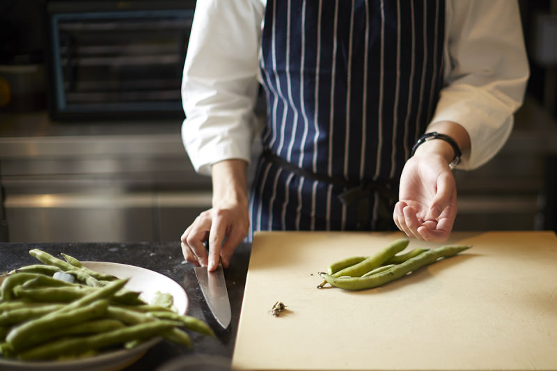 A chef chops broad beans on a chopping board